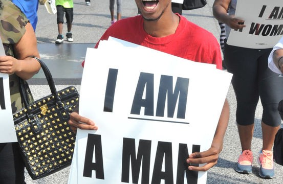 Ferguson protest: 'I am a man' Rafhen Aldridge marches down South Florissant Rd. with about 200 protesters in Ferguson, Mo. protesting police brutality by their department Monday morning.  Photo by Wiley Price / St. Louis American.