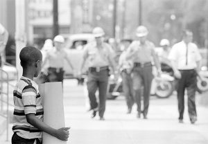 Deputies approach child demonstrator in front of the Dallas County courthouse in Selma, Alabama, July 8, 1964. Photography by Matt Herron.