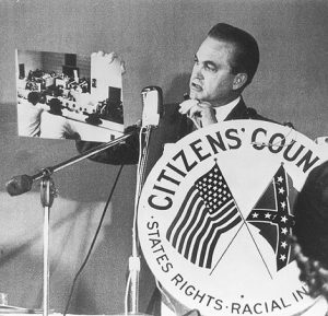 "Alabama Governor George Wallace, holding photograph of alleged ""known agitators"", while speaking to Citizens' Council group in Atlanta in 1963. Library of Congress."