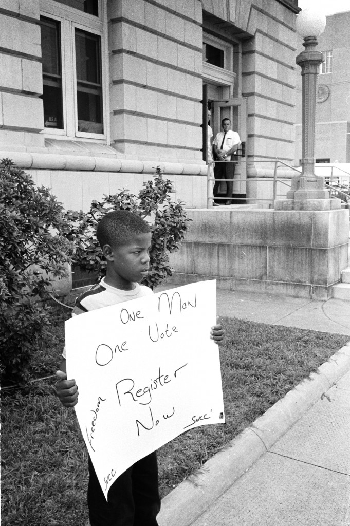 A brave young boy demonstrates for freedom in front of the Dallas County courthouse in Selma on July 8, 1964. Selma sheriff deputies approach and arrest him. Photos used by permission of Matt Herron/Take Stock Photos.