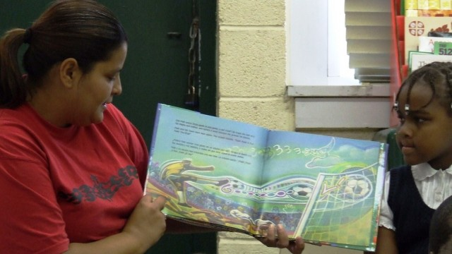 Parent reads book about soccer in a classroom.